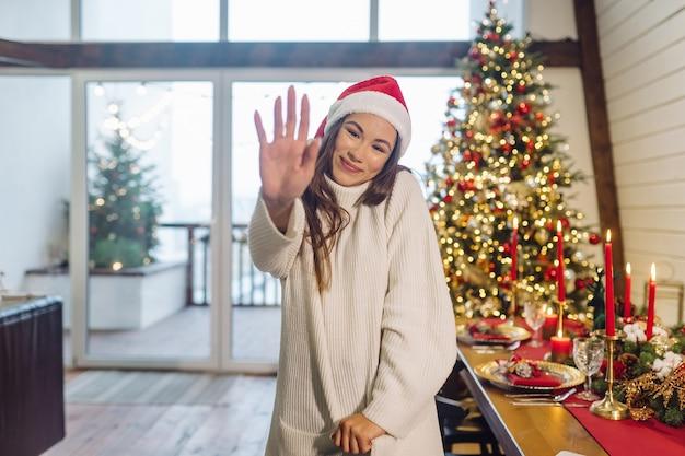 Девушка машет рукой на камеру в канун нового года.