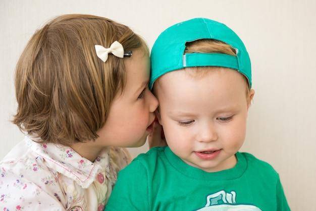 Девочка шепчет мальчику на ухо секрет