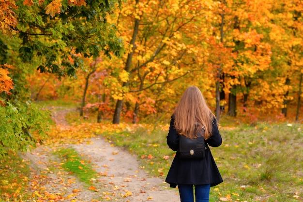 Девушка с рюкзаком гуляет по дороге в парке осенью.