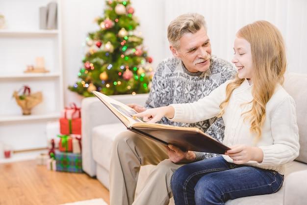 할아버지와 함께 크리스마스 트리 근처에서 사진첩을 보는 소녀