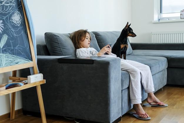 Девушка со смартфоном смотрит на экран. рядом с ней собака.