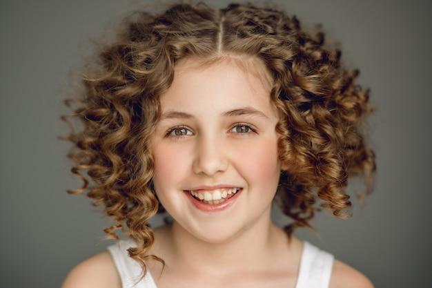 곱슬 머리의 소녀는 아름답게 미소를 짓고 그녀의 시선은 프레임으로 똑바로 향합니다.