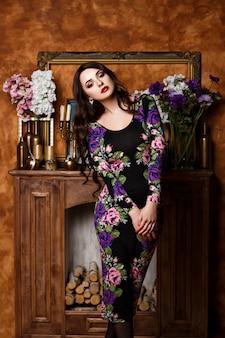 花を持つ少女が暖炉のそばに立っています。