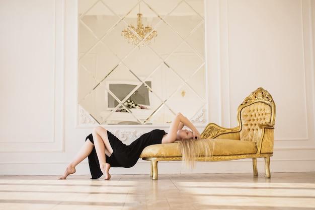 長いブロンドの髪を持つ少女。黒のドレスを着た女性はソファーに横になっています。美しい姿。