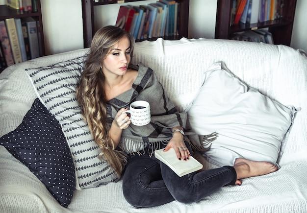 Девушка с длинными волосами, удобно одетая, читает книгу и пьет кофе на диване на фоне библиотеки