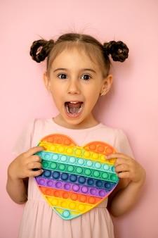 おさげ髪の女の子は、ハートの形をしたポピーのおもちゃを手に持って片目を閉じて驚いて目を膨らませました。