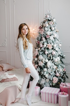 Девушка с подарками возле елки с новым годом и рождеством