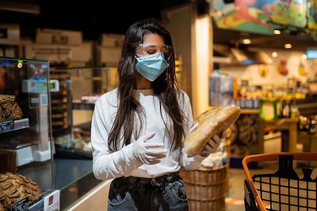 수술 용 마스크를 쓴 소녀가 빵을 사러갑니다.