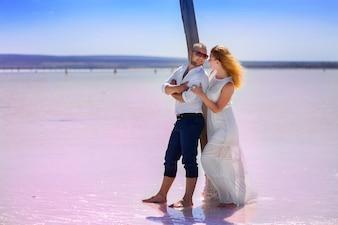 男と女は山の背景に塩味の湖で屋外でポーズします。