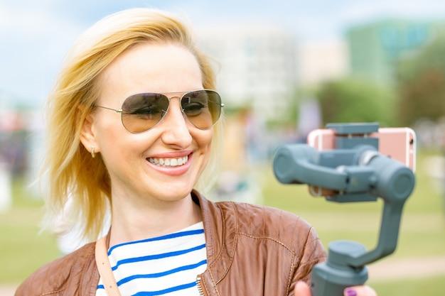 Девушка с телефоном на стабилизаторе ведет видеоблог. она берет себя на камеру смартфона