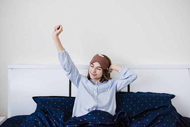 Девушка проснулась и лежит в пижаме на белой кровати. синий ли