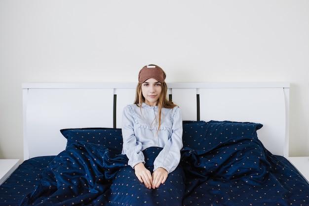 Девушка проснулась и лежит в пижаме на белой кровати. синее постельное белье. с завязанными глазами на голове. маска для сна.