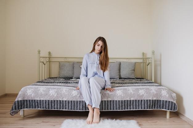 Девушка проснулась и сидит в пижаме на кровати в своей комнате. стильный серо-белый интерьер.
