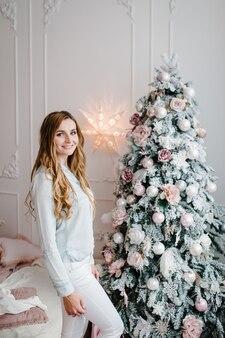 Девушка, женщина возле елки. счастливого рождества. рождественский интерьер. концепция семейного зимнего отдыха.