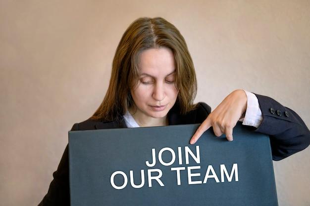 Девушка женщина встает и указывает пальцем на надпись на черной доске присоединяйтесь к нашей команде