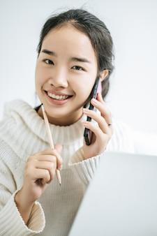 소녀는 흰 셔츠를 입고 전화 통화를하며 행복하게 연필을 들고있었습니다.