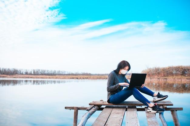 女の子は新鮮な空気の中でコンピューターで働いています。リモートワーク。