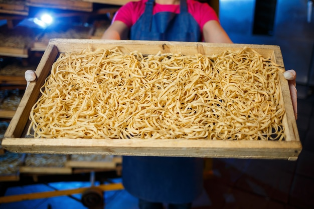 女の子はスパゲッティの生産に取り組んでいます。麺作り。パスタ工場。パスタの段階的生産。生麺。パスタの箱を持った労働者。