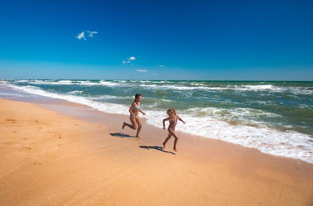 Девушки, наслаждаясь теплым ветерком, бегают по волнам.