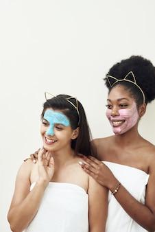 Лица девушек покрыты розовыми и голубыми масками для ухода за лицом. красота лица, концепция спа