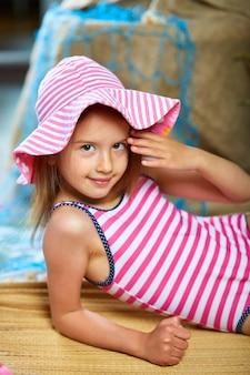 분홍색 모자를 쓴 소녀들은 바다 또는 바다 근처의 가상 해변에 누워 일광욕을합니다. 가정 격리에서 여름 바다 해변 휴가를 모방합니다. 코로나 바이러스 가정 활동, 재미 있고, 행복하고, 미친.