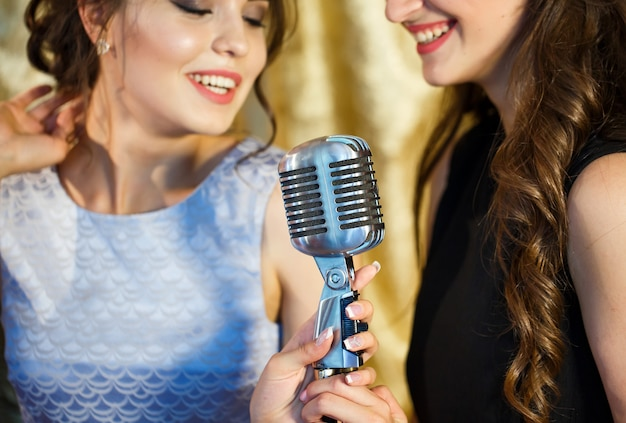 Девушки поют караоке в ресторане.