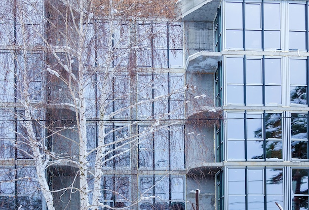 고층 건물에 있는 주거용 아파트의 유리 외관. 현대적인 건물 디자인의 창문과 발코니.
