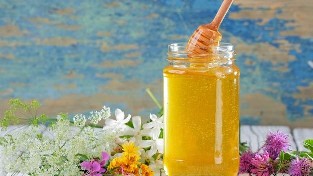 素朴な背景に新鮮な蜂蜜とガラスの瓶。テーブルの上の花。