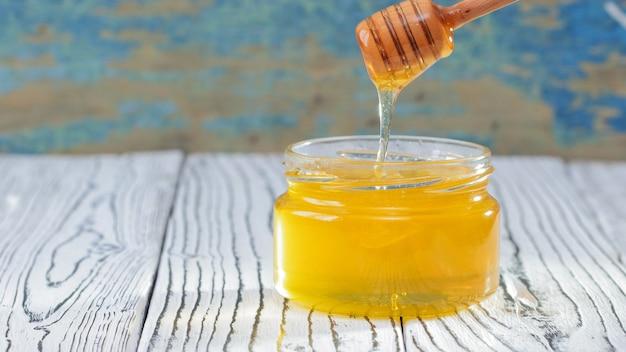 素朴な背景に新鮮な蜂蜜とガラスの瓶。蜂蜜の背景