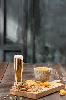 ビールとポテトチップスのグラス、白で分離されたピスタチオ
