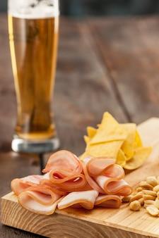 맥주 한 잔과 감자 칩, 흰색으로 분리된 피스타치오