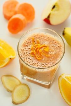 Стакан фруктового и овощного смузи. рядом морковь, банан, апельсин, яблоко и имбирь.