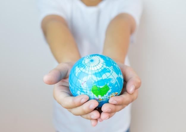 子供の手の中にある世界。環境、教育コンセプトのコンセプト