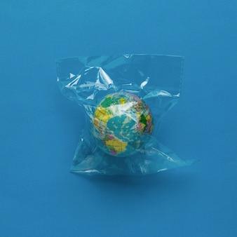 地球儀は青い背景のセロハンバッグに詰め込まれています。フラットレイ。