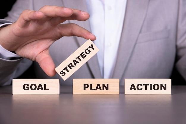 目標、計画、戦略、行動、テキストは木製の立方体に書かれています Premium写真