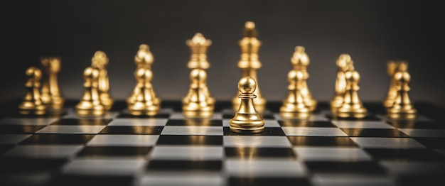 Золотая шахматная команда, стоящая на шахматной доске