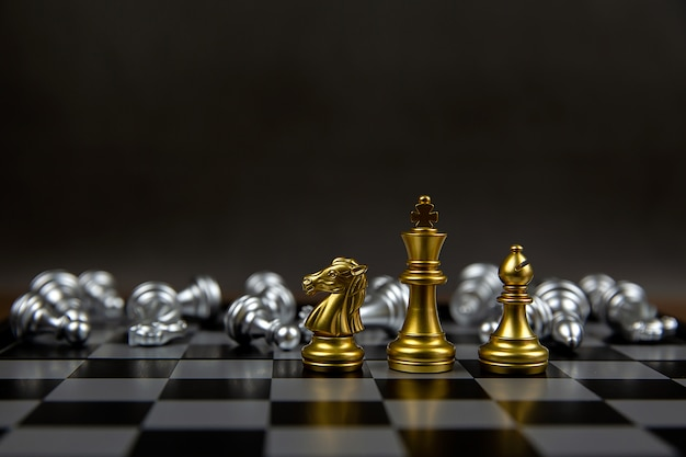 Золотая шахматная команда стоит посреди падающих серебряных шахмат.