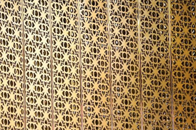 タイのどこかの壁の背景にゴールデンクラフトタイパターンポップアップ。