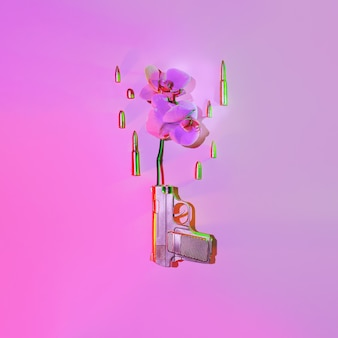 Золотая пушка стреляет в цветок орхидеи, рядом летят пули на розовом фоне, концепция против войны.