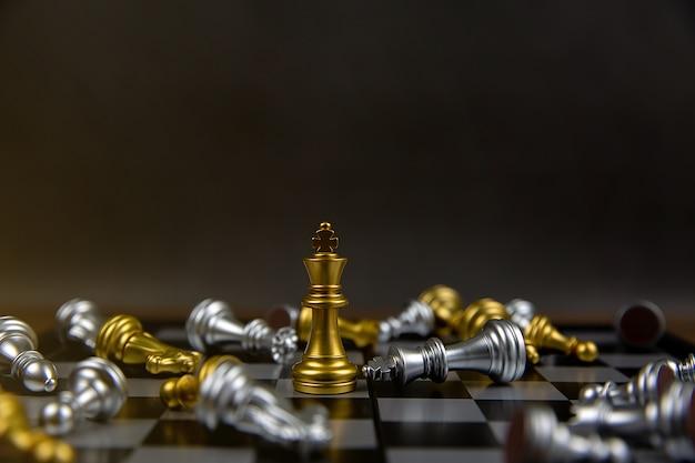 他のチェスの真ん中に立っている黄金の王チェスが落ちています。