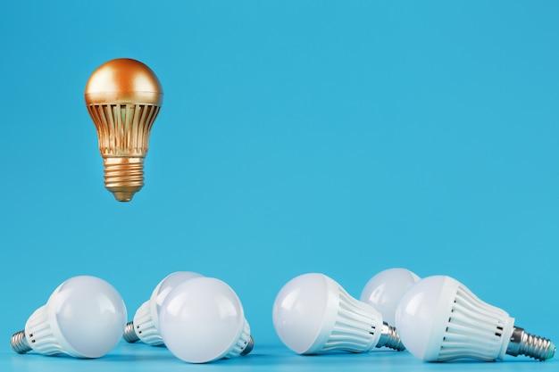 Золотая лампочка поднимается и парит над окружением обычных лампочек.