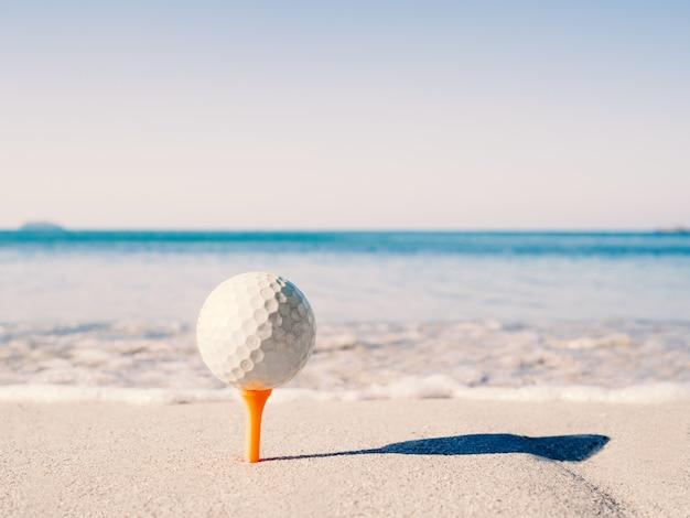 골프공은 티 위에 있고, 바다를 배경으로 모래 해변에 수놓아져 있습니다.