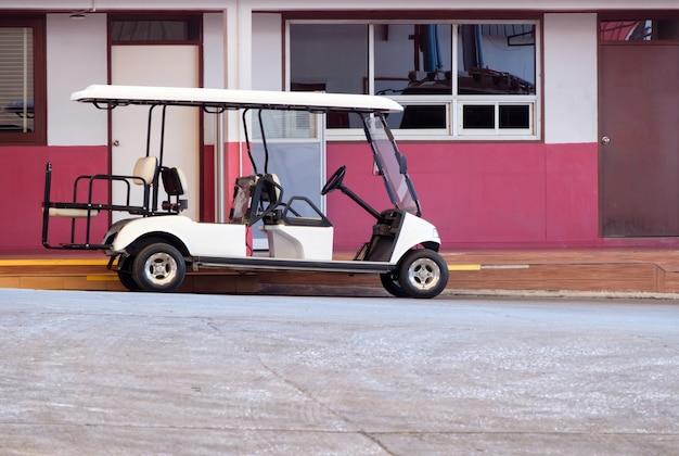 골프 카트는 큰 공장 주변을 순찰하기 전에 충전기 사무실 근처에 주차되어 있으며 복사 공간의 측면도입니다.