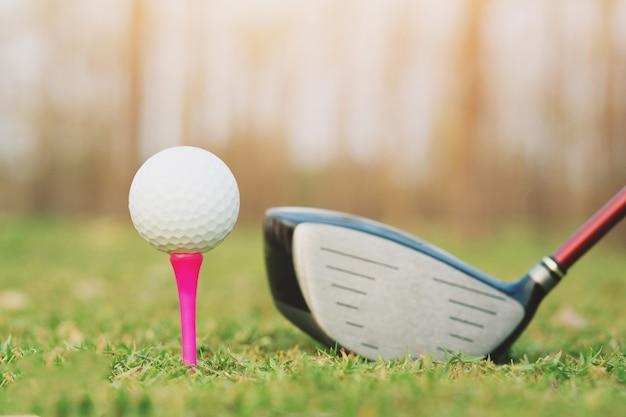 ゴルフ クラブとゴルフ ボールは、日没と夕方の良い天気の芝生のフィールドでクローズ アップ。