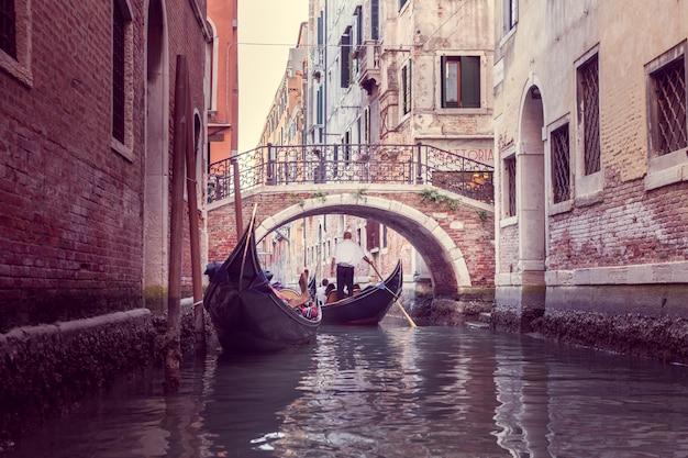 Гондольер плывет по узкому каналу в венеции