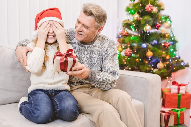 小さな女の子にギフトボックスを与える祖父