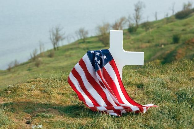 兵士の墓。死んだ兵士の墓の上にアメリカの国旗。墓で軍帽