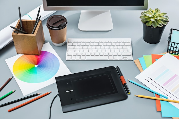 노트북이있는 회색 책상, 빈 시트가있는 메모장, 꽃 냄비, 스타일러스 및 수정을위한 태블릿