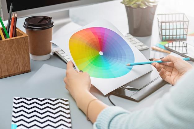 노트북, 빈 시트가있는 메모장, 꽃 냄비, 스타일러스 및 수정 용 태블릿이있는 회색 책상