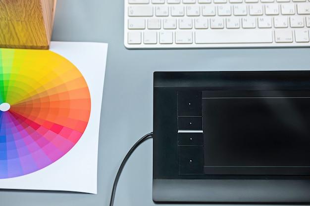 ノートパソコン、空白シート付きメモ帳、花のポット、スタイラス、レタッチ用タブレットを備えたグレーのデスク